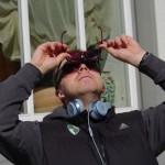 Baubas stebi saulės užtemimą per patamsintus akinius